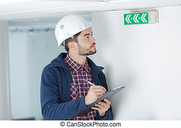 Inspector looking at arrowed exit sign