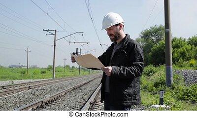 Inspector of railway traffic talking on walkie-talkie. Railway worker in white helmet holding blueprints plan.