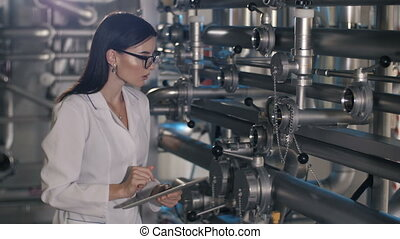 Inspector takes readings of meters at the factory - Woman...