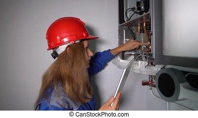 Inspector technician woman inspecting gas boiler heating ...