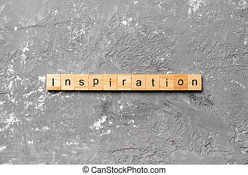 Inspiration word written on wood block. Inspiration text on cement table for your desing, concept