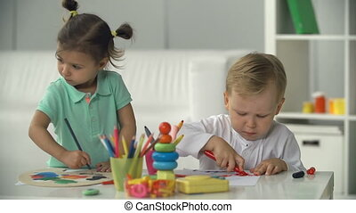 Inspirational Company - Two charming toddlers absorbed in...