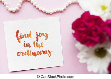 Inspirational quote Find joy in the ordinary written in calligraphy style with watercolor. Composition on a pink background. Flat lay