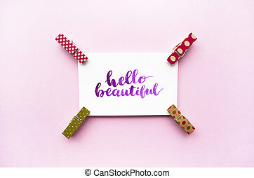 Inspirational quote Hello beautiful handwritten with watercolor in calligraphy style, miniature clothespins on a pink background. Flat lay