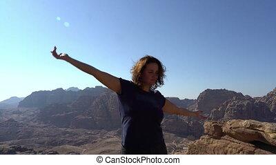 Inspirational woman enjoy life, dancing outdoors at the edge...