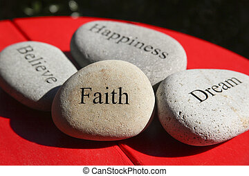 rocks, stones, with inspirational words carved on them, sitting on a red table top