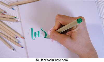 Inspire. Calligrapher writes with green marker word on white...