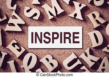 Inspire Concept Word - Corkboard covered with word Inspire...