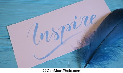 Inspire text. Beautiful font of lettering motivational word on white canvas with blue ink. Background. Graphic design, handwriting, creation concept. 4k.