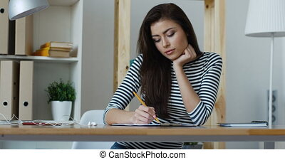 Inspired beautiful young business woman making some notes holding her chin with hand looking for ideas