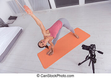 Inspired blogger doing exercises while making a video