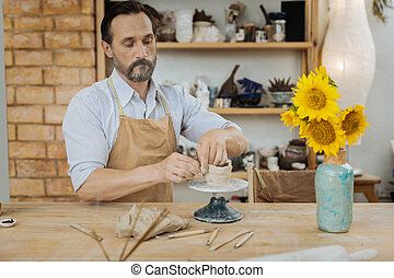 Inspired ceramist making his famous vases for flowers -...