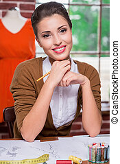 Inspired fashion designer. Beautiful young fashion designer holding pencil and smiling at camera while sitting at her working place