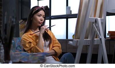 Inspired female artist thinking about her painting -...