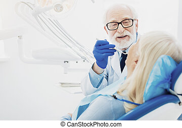 Inspired male dentist examining mouth cavity