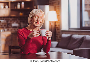 Inspired woman having coffee and relaxing