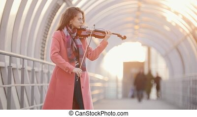 Inspired woman playing violin on the street, mid shot