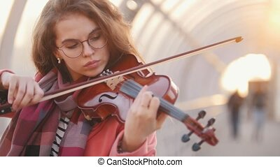 Inspired young woman playing violin solo on the street, mid...