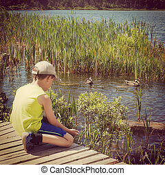 instagram of young boy feeding ducks from his hand