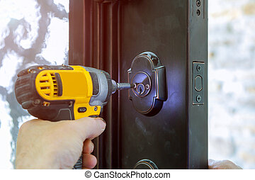 Install the door handle with a lock, Carpenter the screw, using an drill screwdriver, close-up.