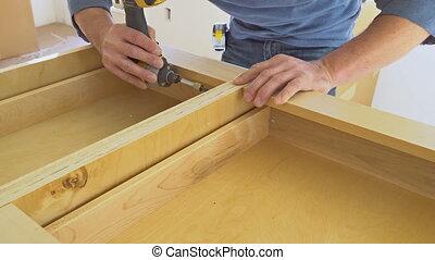 Installation kitchen. Worker installs doors to kitchen...