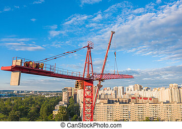 Installation of a construction crane, with the help of a crane on a truck, aerial view. In the background, urban view, residential high-rise buildings, real estate.