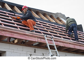 installation of a roof - Worker installs bearing laths on...