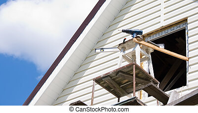 Installation of a siding on a house against the sky