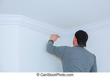 Installation of ceiling moldings. Worker fixes the wood molding to the ceiling