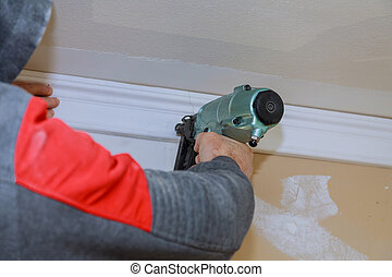 Installation of crown moldings trim on the ceiling of the using gauge finish nailer