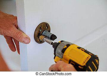 Installation of door lock using a screwdriver to. Carpenter...