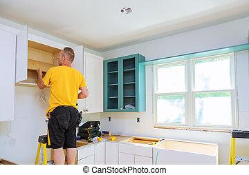 Installation of kitchen. Worker installs doors to kitchen cabinet.