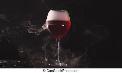 installation of smoke in glass with wine on black background