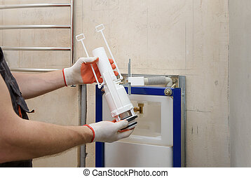 Installation of toilet siphon. - A worker is inserting a...