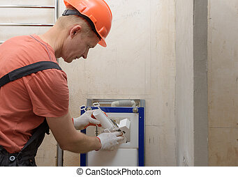 Installation of toilet siphon. - The worker is inserting the...