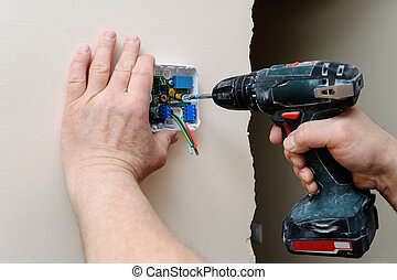 Installing a programmable room thermostat. Man's hands...