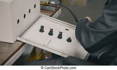 installing a sealing strip to the door of electrical cabinet Hands of electrician install and tighten up the nuts key equipment in the industrial fuse box
