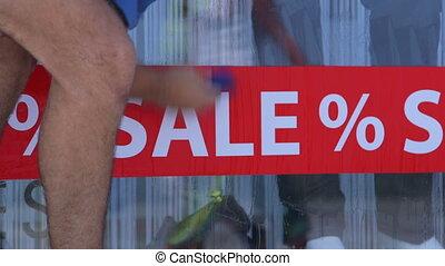 Installing Advertising Sticker SALE % in Retail Shop Window...