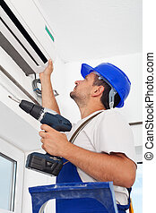 Installing air conditioning unit - Worker installing air...