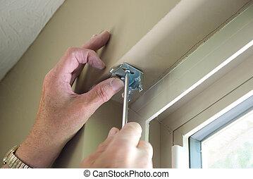 Hands installing blind hardware onto window frame