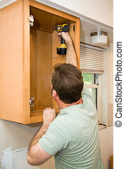 Installing Cabinets - Carpenter screwing solid maple...