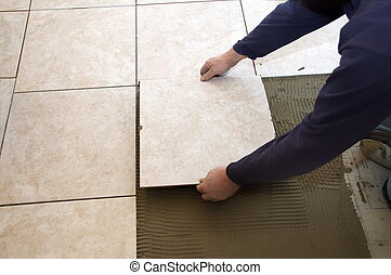 Installing Ceramic Tile - A man on his knees installing a...