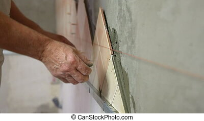 Installing Ceramic Tile - Man's hands wiping grout from a...
