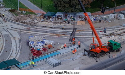 Installing concrete plates by crane at road construction...