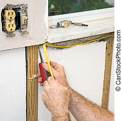 Closeup of electrician's hands as he installs electric wiring in styrofoam insulation. Authentic and accurate content depiction in accordance with industry code and safety regulations.