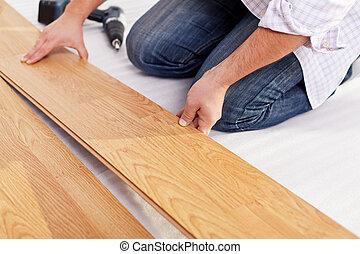 Installing laminate flooring fitting the next piece - focus...