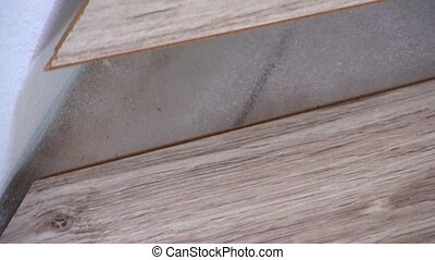 Installing laminate on floor - close up of male hands...