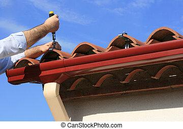 Installing rain gutter - Man installing pvc rain gutter...
