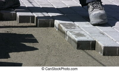 Installing Sidewalk Bricks - A worker patiently installs...