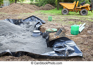 Installing the sand filter on a septic tank showing the liner , sand, filter and pump